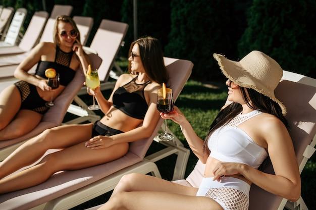 Dames met cocktails vrije tijd op ligbedden