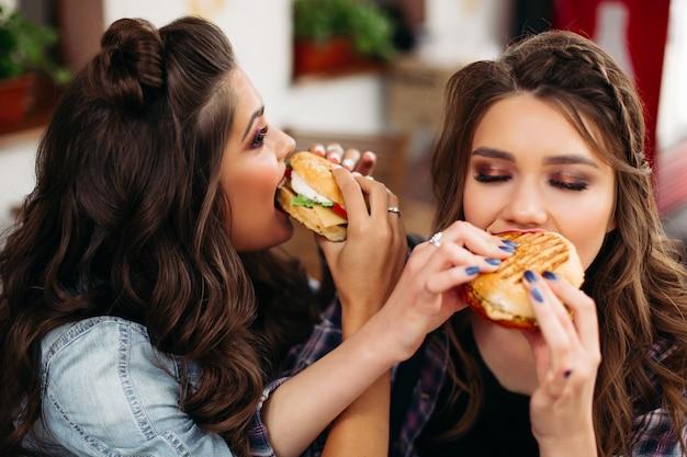 Dames met kapsel en make-up genieten van hun hamburgers.
