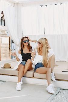 Dames met wijnstok. meisjes in top en korte broek. vrienden in een zonnebril.