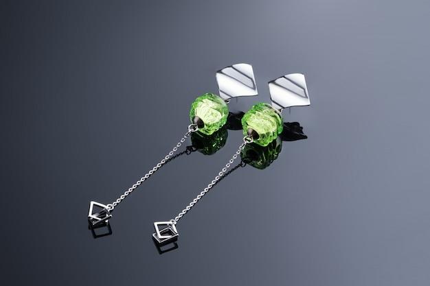 Dames oorbellen met een groene steen, handgemaakte sieraden op een zwart kleurverloop oppervlak