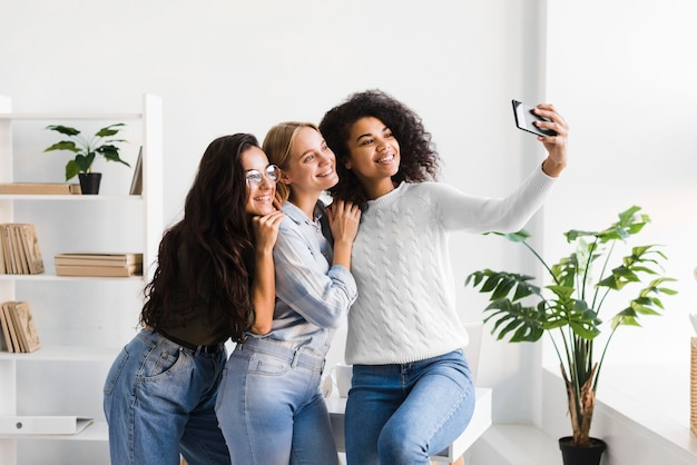 Dames op kantoor die selfies nemen