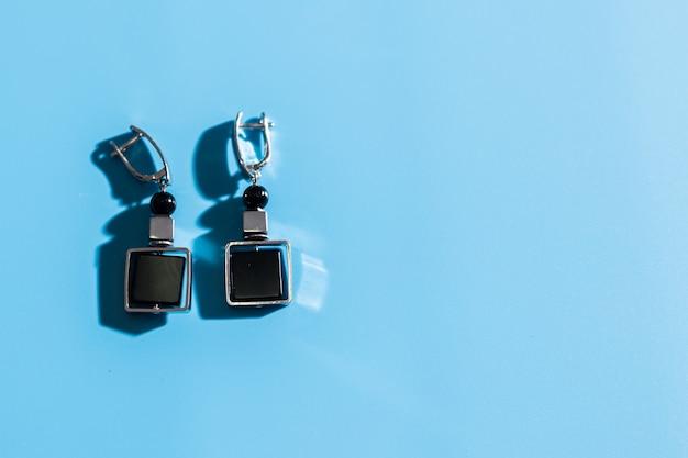 Dames sieraden. trendy sieraden op blauwe muur. plat lag, bovenaanzicht. kopieer ruimte.