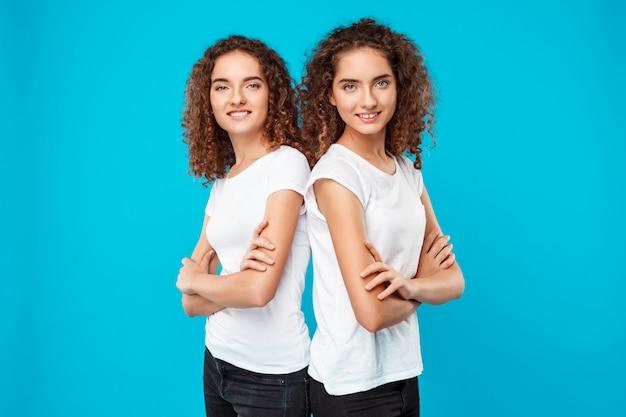 Dames tweeling poseren met gekruiste armen, glimlachend over blauw.