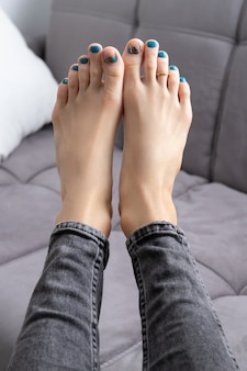 Dames voeten in jeans met pedicure op grijze bank thuis. mooie zomerse turquoise nageldesign