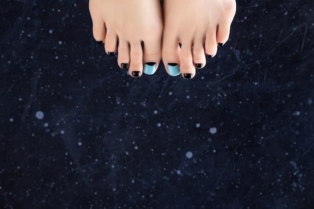 Dames voeten op donkere achtergrond. prachtige lente zomer blauw en zwart nageldesign. manicure, pedicure schoonheidssalon concept.