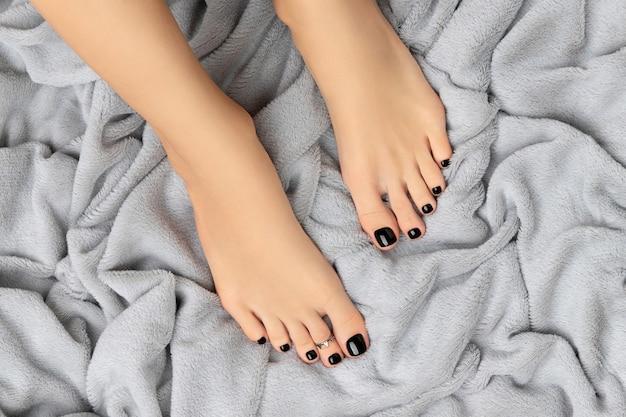 Dames voeten op harige grijze achtergrond. prachtig klassiek zwart nageldesign. manicure, pedicure schoonheidssalon concept.