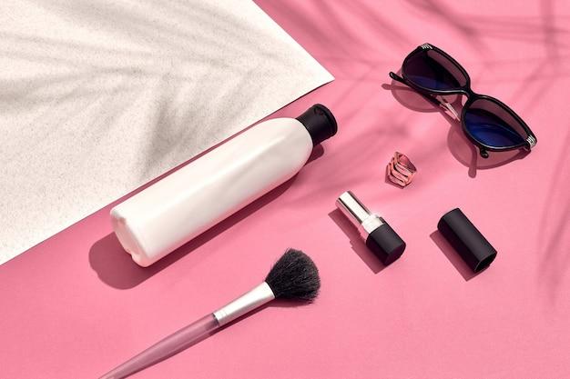 Damesaccessoires liggend plat op getextureerd papier roze en witte pastelkleuren als achtergrond met kopieersp...
