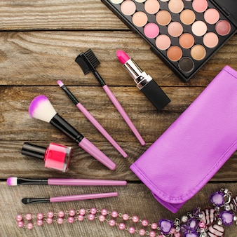 Damesaccessoires: make-uptas, make-upborstels, ketting, nagellak, lippenstift. bovenaanzicht.