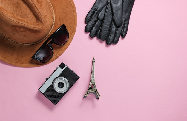 Damesaccessoires, retro camera, beeldje van de eiffeltoren op roze achtergrond. bovenaanzicht