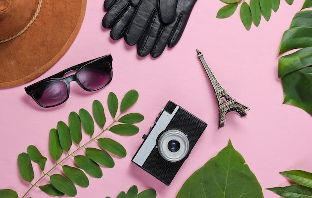 Damesaccessoires, retro camera, beeldje van de eiffeltoren op roze pastel achtergrond met groene bladeren. bovenaanzicht
