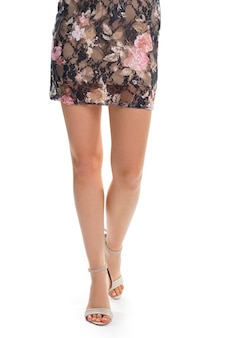 Damesbenen in beige hakken. gebloemde jurk met beige voering. modieus roze patroon. elegante schoenen van designer.