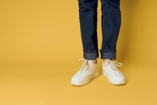 Damesbenen jeans witte sneakers mode straatstijl geel