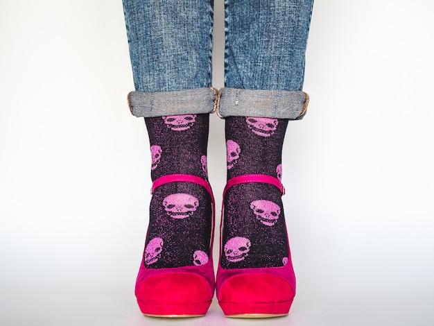 Damesbenen, trendy schoenen, blauwe spijkerbroek en bonte, lange sokken op een witte, geïsoleerde achtergrond. detailopname. concept van stijl en elegantie
