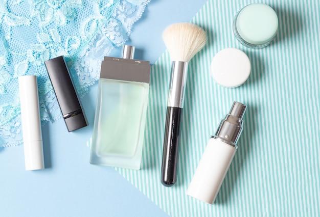 Damescosmetica en accessoires op een blauw gestreepte achtergrond: parfum, crème, lippenstift, make-upborstel. mode en schoonheidsconcept.