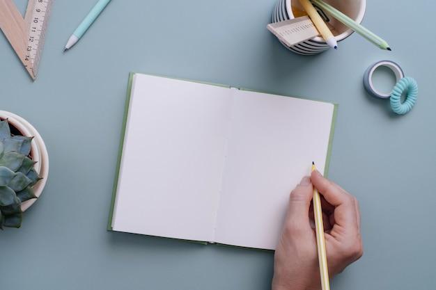 Dameshand klaar om in het lege notitieboekje te schrijven