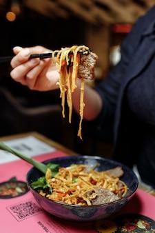 Dameshand met eetstokjes. vrouwelijke hand met stokjes neemt noedels en eet