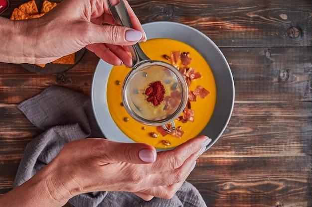 Dameshanden bestrooid met zeefpaprika op traditionele pompoenpureeroomsoep met wortelen