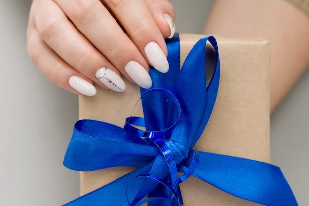 Dameshanden met mooie nagels en design bevat een geschenkdoos met satijnen lint.