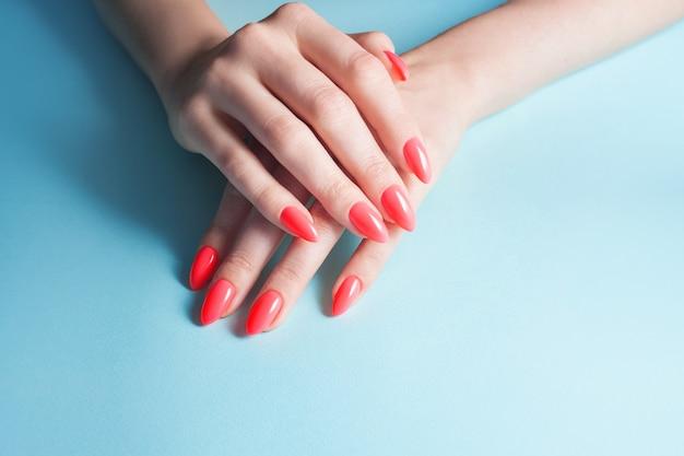Dameshanden met perfecte rode manicure. nagellak rood koraal kleur.