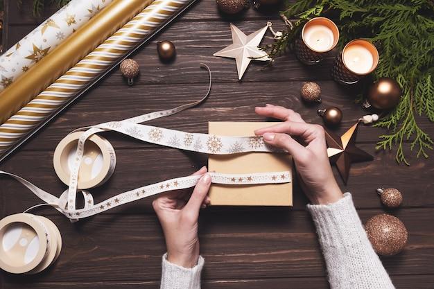 Dameshanden pakken een feestelijk lint op voor het inpakken van een kerstcadeau creatieve doe-het-zelf hobby