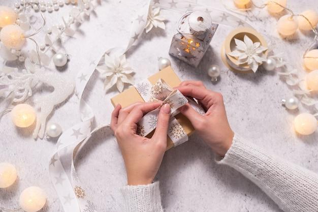 Dameshanden versieren kerstcadeau met wit lint en decoreren kerstmis en nieuwjaar