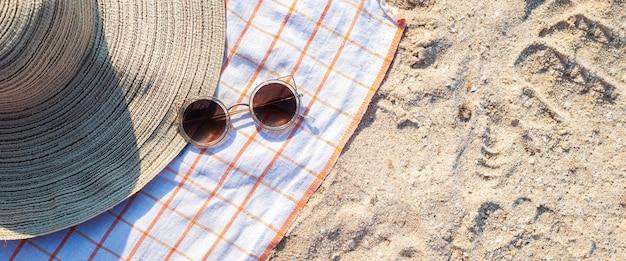 Dameshoed, bril op het zandstrand. bovenaanzicht, plat gelegd. banier.
