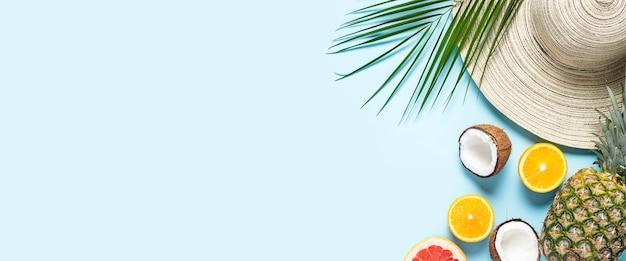 Dameshoed met brede rand, tropisch fruit en een tak van een palmboom op een blauwe achtergrond.