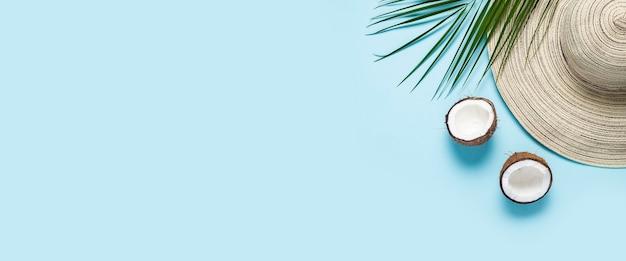 Dameshoed met brede rand, zonnebril, kokosnoot en een tak van een palmboom op een blauwe achtergrond.