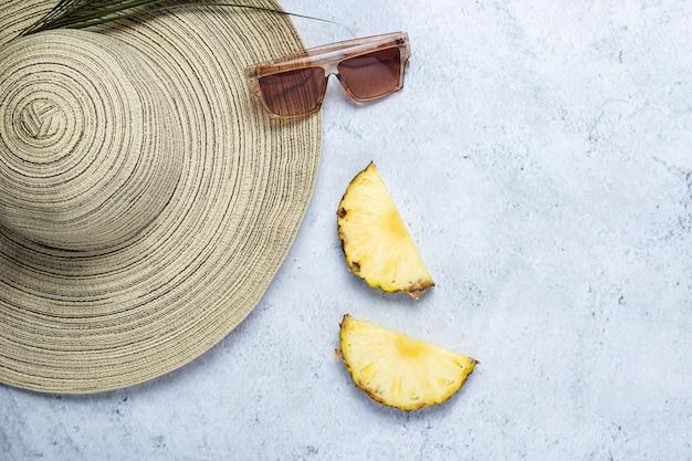 Dameshoed, zonnebril, ananasschijfjes, palmblad op een betonnen ondergrond. bovenaanzicht, plat gelegd.