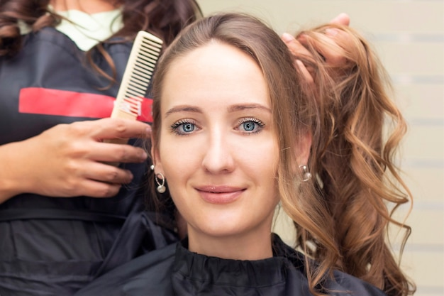 Dameskapper, schoonheidssalon. close up van een kapper die een kapsel doet.