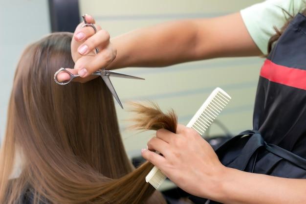 Dameskapper, schoonheidssalon. professionele stylist knipt vrouwelijk haar in salon