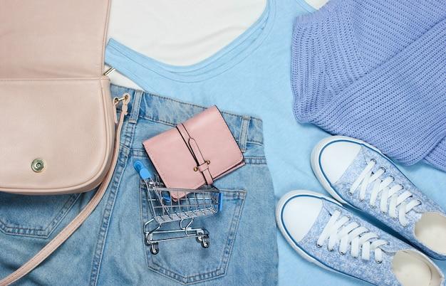Dameskleding en accessoires. sneakers, t-shirt, tas, jeans, mini-winkelwagentje