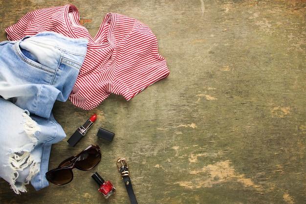 Dameskleding en accessoires voor de zomer: t-shirt, jeans, lippenstift, nagellak, riem, zonnebril. bovenaanzicht.