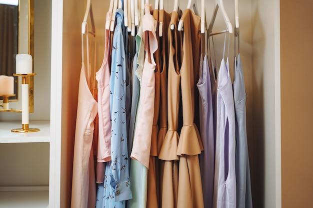 Dameskleding, jurken en blouses aan kleerhangers in een kleedkamer of winkel.