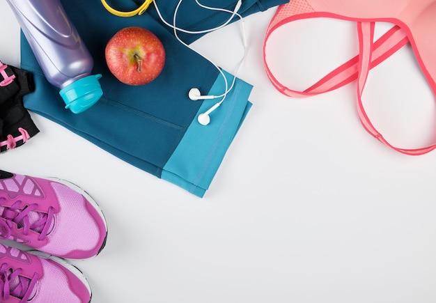 Dameskleding voor fitness, fles, hoofdtelefoons en sneakers