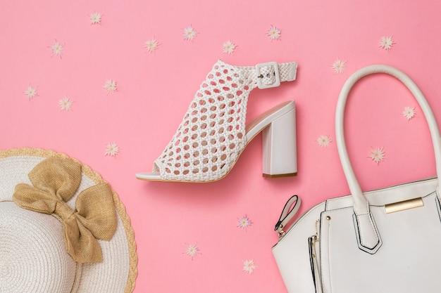 Damesmode-accessoires en schoenen op roze achtergrond met bloemen. zomerschoenen voor dames. plat leggen. het uitzicht vanaf de top.