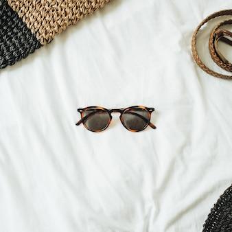 Damesmode-accessoires met bril in het midden van de foto en riem, strooien hoed, strooien tas liggend op bed met wit laken