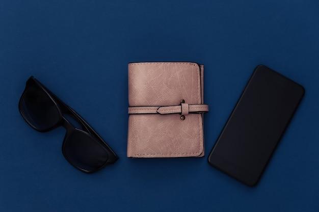 Damesmodeaccessoires en smartphone op een klassieke blauwe achtergrond. kleur 2020. bovenaanzicht.