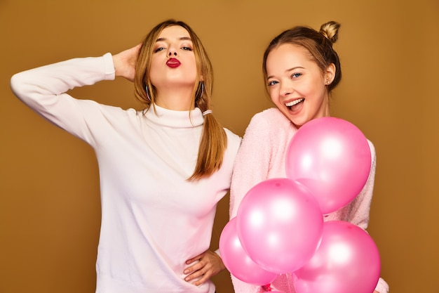 Damesmodellen met roze luchtballonnen op gouden muur