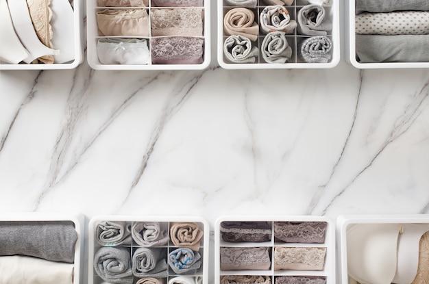 Damesondergoed, pyjama's en sokken netjes opgevouwen en in de ladeverdeler van de kastorganisator op een witte marmeren tafel geplaatst.