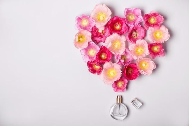 Damesparfumfles en roze kaasjeskruidbloemen. minimalisme schoonheid concept.