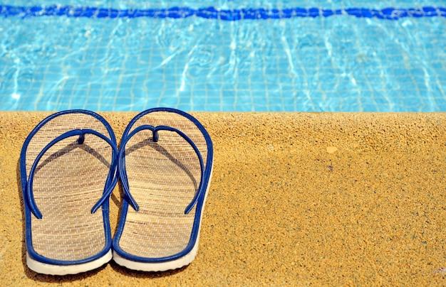 Damessandalen aan de voeten van het zwembad