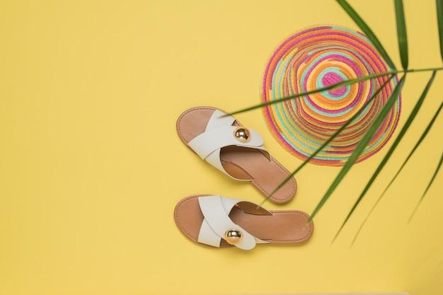 Damessandalen en een kleurrijke hoed onder de bladeren van een palmboom. het concept van zomervakantie en reizen.