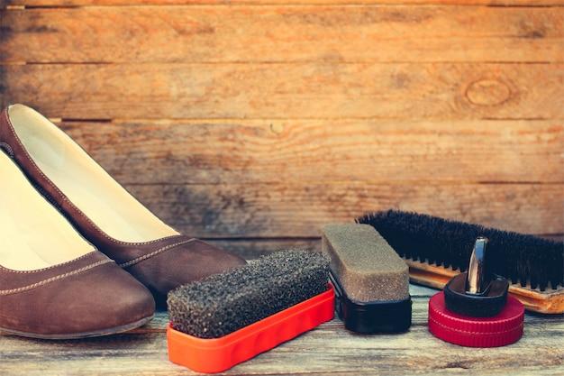 Damesschoenen en verzorgingsproducten voor schoeisel op houten achtergrond.