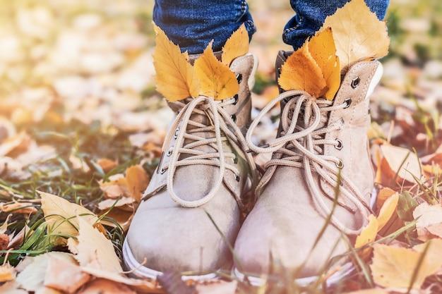 Damesschoenen in kleurrijke bladeren in het herfstseizoen