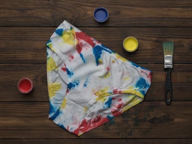 Damesslipje in de stijl van tie dye en verf op een donkere houten ondergrond. gekleurd ondergoed in huis.