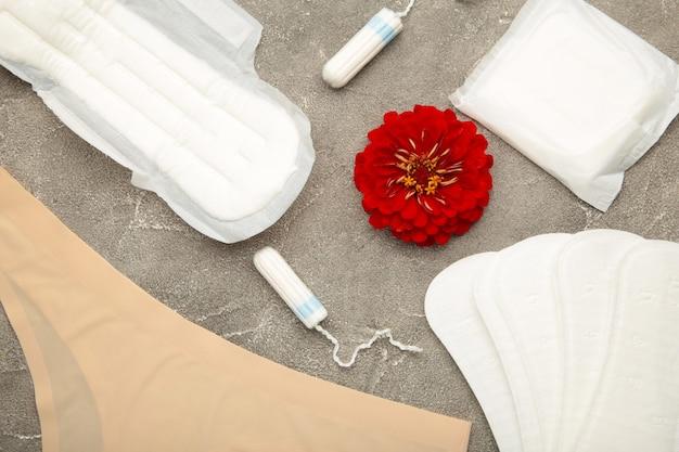 Damesslipje met maandverband en tampons op grijze achtergrond. bovenaanzicht. concept van kritieke dagen, menstruatie, vrouwelijke hygiëne. bovenaanzicht