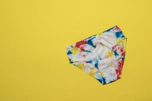 Damesslipjes zijn met de hand beschilderd in de stijl van tie dye op een felgele achtergrond. gekleurd ondergoed in huis.