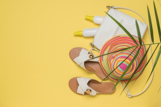 Damestas met zonnebrandcrème, hoed en sandalen op een gele achtergrond. vakantieconcept. plat leggen.