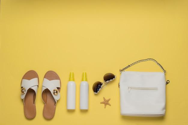 Damestas, sandalen en zonneproducten. vakantie concept. plat leggen.